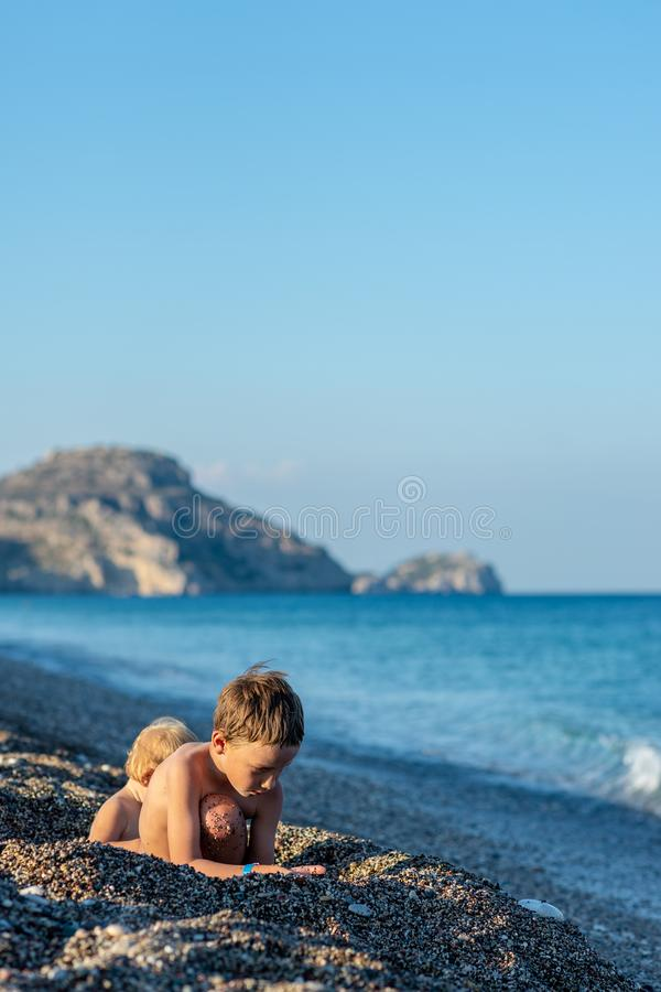 Dwa berbecia dzieciaka bawić się w dziurze kopali w otoczak plaży zdjęcie stock