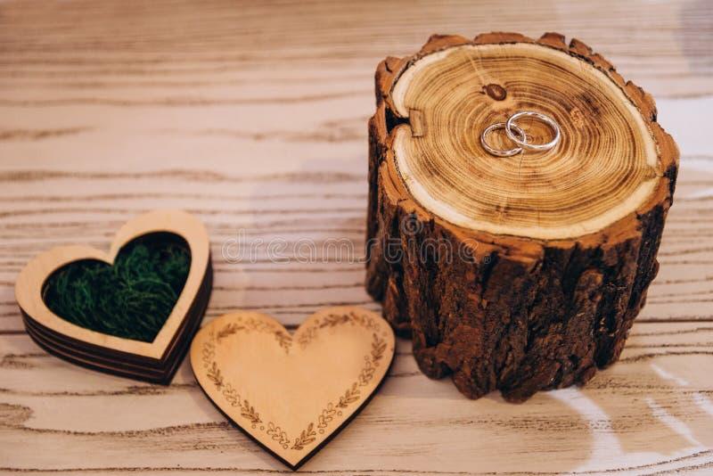 Dwa białego złota pierścionku zaręczynowego na drzewie z drewnianym pudełkiem na którym pali piękny wzór na lekkim drewnianym sto fotografia stock