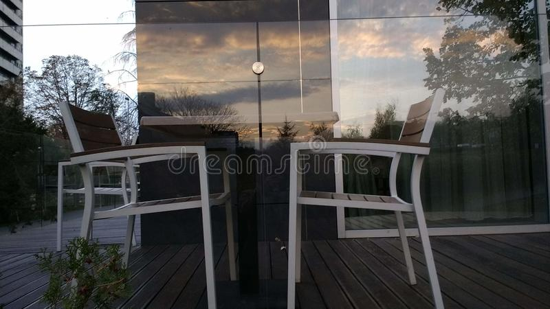 Dwa białe krzesła stolik i niebo w szklanym ogrodzeniu zdjęcie royalty free