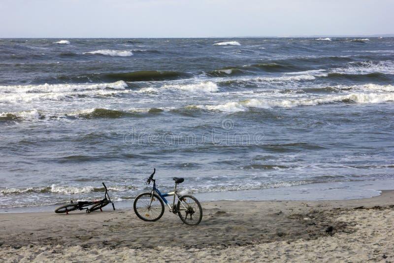 Dwa bicyklu na piaskowatej plaży przeciw falom morze bałtyckie zdjęcia royalty free