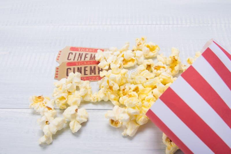 dwa bileta kino wraz z pakunkiem rozrzucony popkorn na świetle, biały tło zdjęcie royalty free