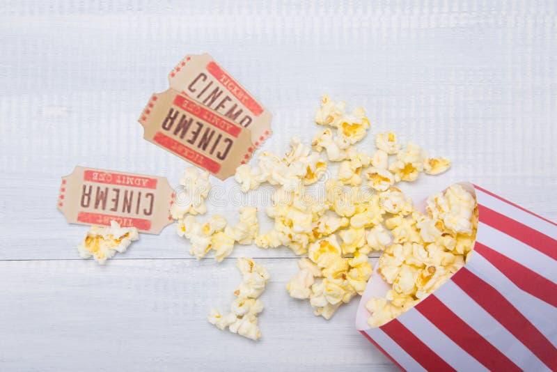 Dwa bileta kino wraz z pakunkiem rozrzucony popkorn na świetle, drewniany tło fotografia stock