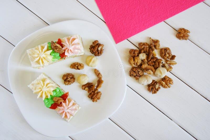 Dwa biskwitowego torta z kremowymi dekoracjami, macadamia dokrętkami i orzechami włoskimi w talerzu na tle, bielu i menchii Drewn obraz stock