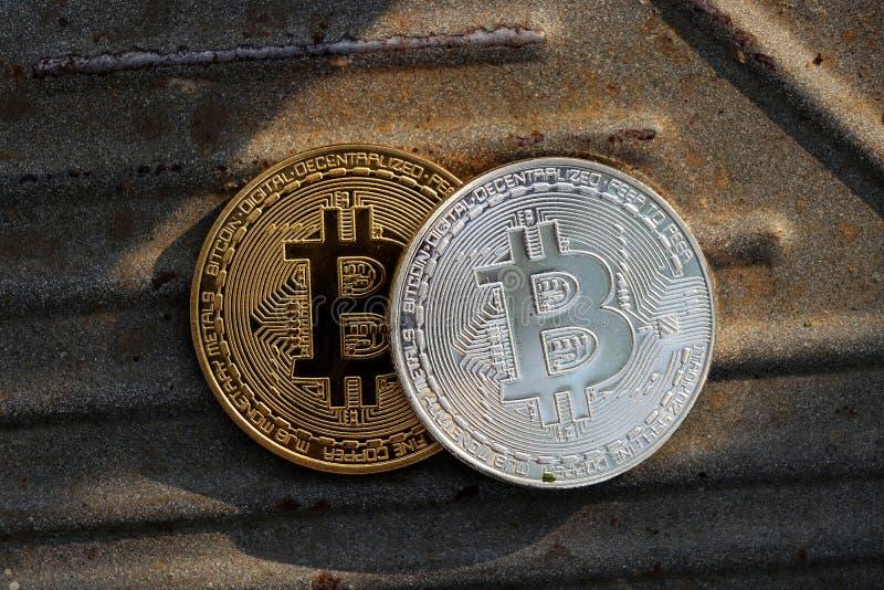 Dwa bitcoins Jeden jest złoty, po drugie jest srebnym bitcoin Oba są na żelazo desce z rdzą zdjęcie stock