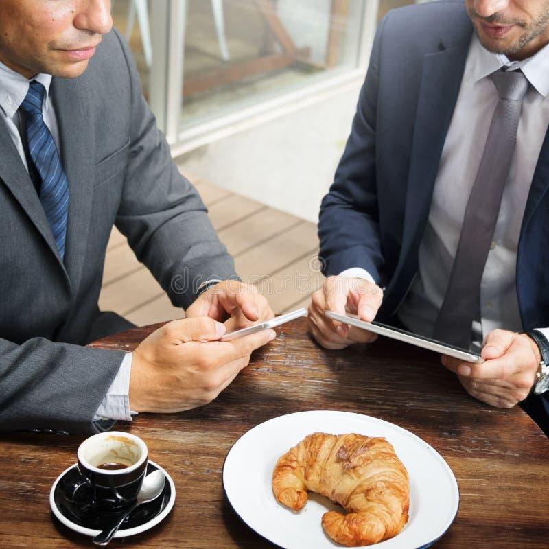 Dwa biznesmenów Cukiernianego spotkania pastylki Bezprzewodowy pojęcie fotografia stock