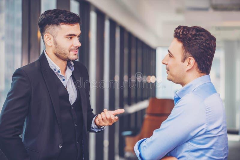 Dwa biznesmenów pozycja i dyskutuje pracy lub projekta strategię Kolega opowiada i pyta dla pracy opinii zdjęcia stock