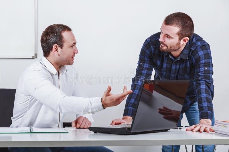 Dwa biznesmena dyskutują przy spotkaniem w biurze obraz stock