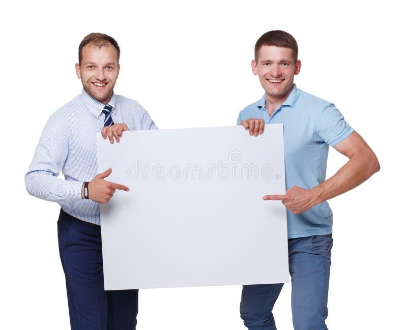 Dwa biznesmena niosą pustą reklamową deskę i pokazują, odosobnioną obraz royalty free