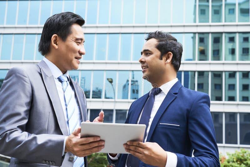 Dwa biznesmena opowiada outdoors obraz stock