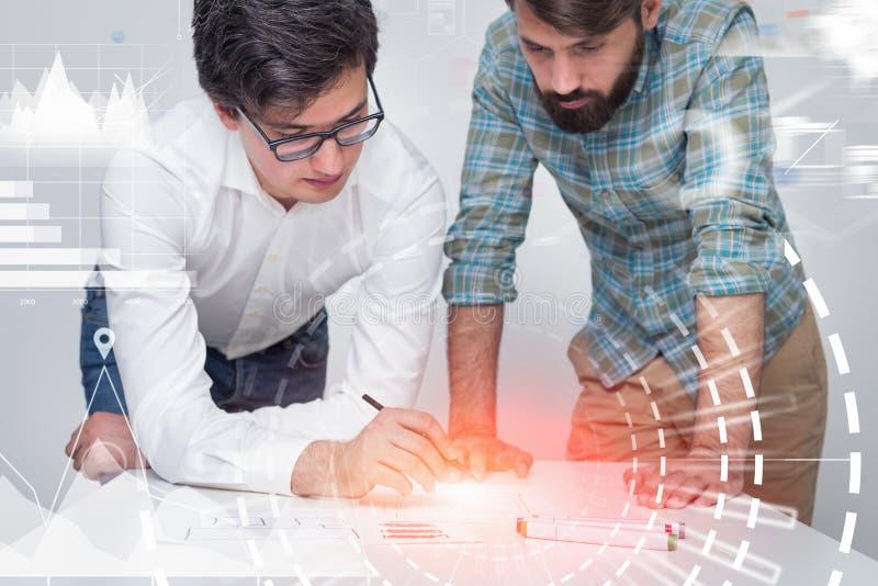 Dwa biznesmena pracuje w biurze, infographics zdjęcie royalty free