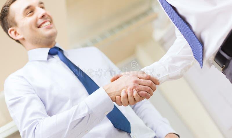 Dwa biznesmena trząść ręki w biurze