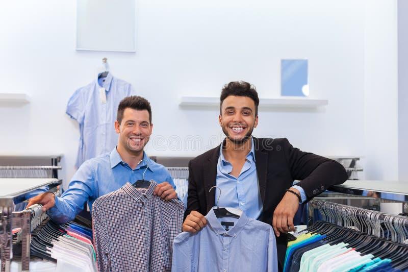Dwa Biznesowego mężczyzna mody Przystojny sklep, Szczęśliwi Uśmiechnięci mieszanki rasy przyjaciół klienci Wybiera Odzieżowe kosz obrazy stock