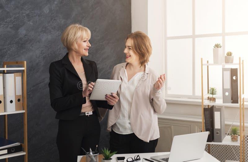 Dwa biznesowych kobiet kolegi pracuje wpólnie na pastylce obraz royalty free