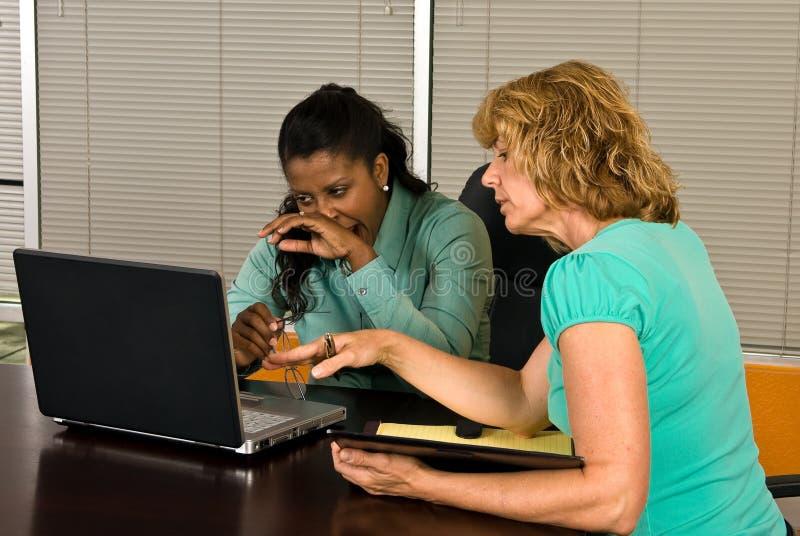 Dwa biznesowych kobiet spojrzenie przy laptopem obraz stock