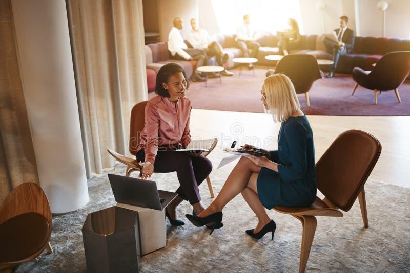 Dwa bizneswomanu dyskutuje pracę na laptopie w biurze zdjęcia royalty free