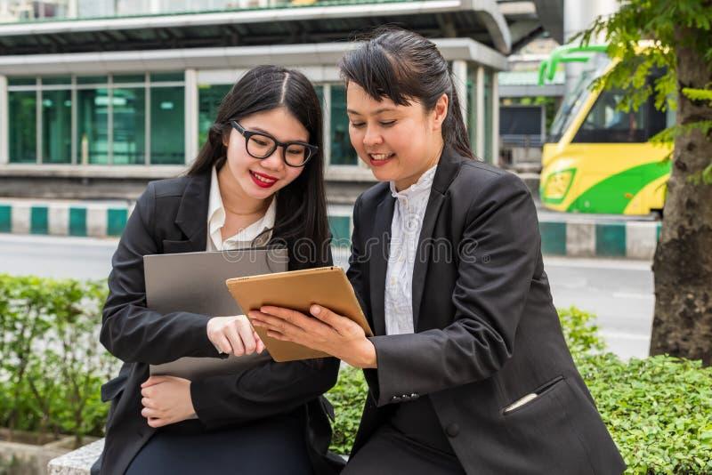 Dwa bizneswomanu patrzeje pastylkę podczas gdy trzymający papierowego segregatoru właściciela zdjęcie royalty free