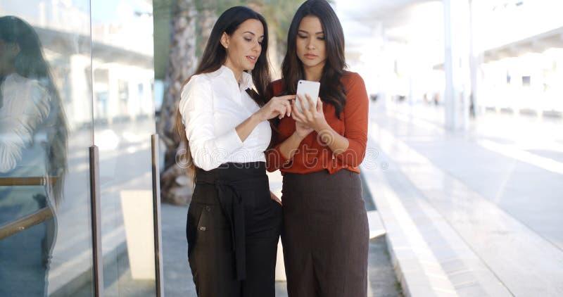 Dwa bizneswomanu sprawdza telefon wiadomość obrazy stock