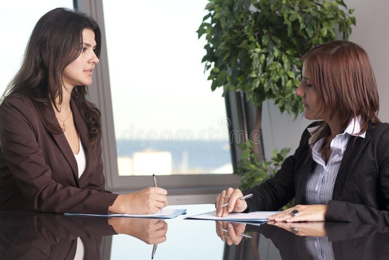 Dwa bizneswomanu target35_1_ przy biurowym biurkiem fotografia stock