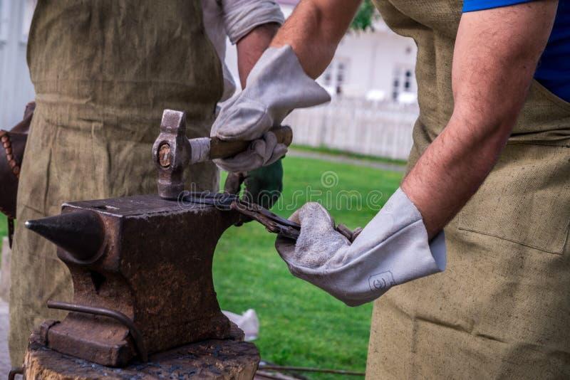 Dwa blacksmiths blisko kowadła Jeden sieka podkowę z baleronem zdjęcie stock