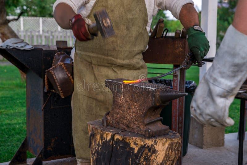 Dwa blacksmiths blisko kowadła Jeden sieka podkowę z baleronem fotografia royalty free