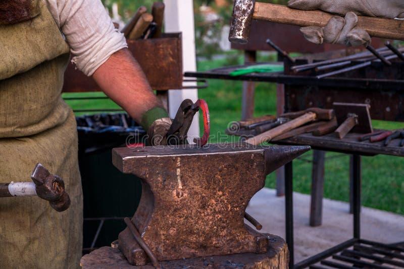 Dwa blacksmiths blisko kowadła Jeden sieka podkowę z baleronem zdjęcie royalty free