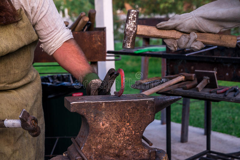 Dwa blacksmiths blisko kowadła Jeden sieka podkowę z baleronem obrazy royalty free