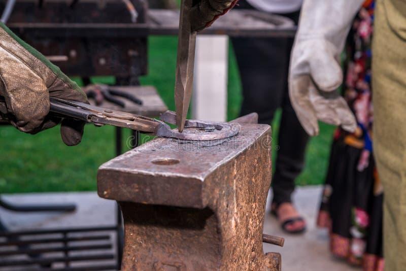 Dwa blacksmiths blisko kowadła Jeden sieka podkowę z młotem W białym kontuszu i rękawiczkach Horyzontalna rama obrazy stock