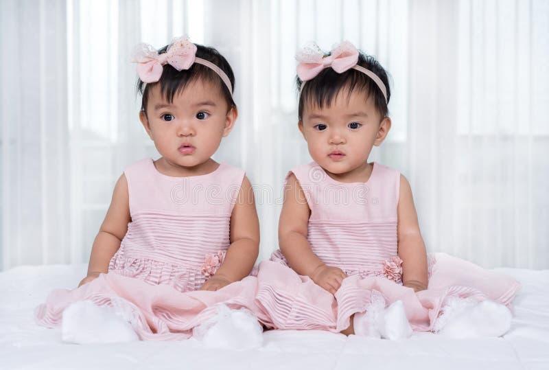 Dwa bliźniaczego dziecka w menchii sukni na łóżku obraz royalty free