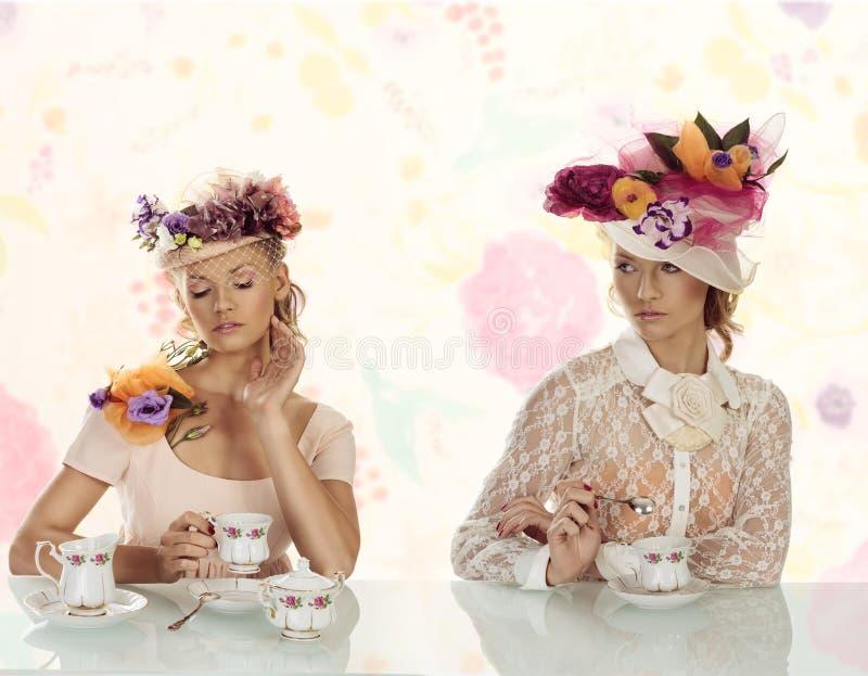 Dwa blonds dziewczyna z kwiatami kapeluszowymi fotografia royalty free