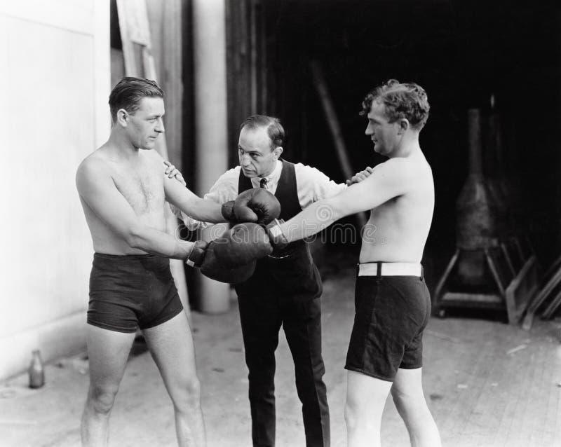 Dwa boksera i arbiter (Wszystkie persons przedstawiający no są długiego utrzymania i żadny nieruchomość istnieje Dostawca gwaranc fotografia royalty free