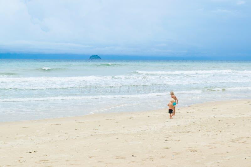 Dwa brata, chłopiec chodzi na białym piasku blisko morza przy plażą, Wietnam, Nha-trang zdjęcie stock