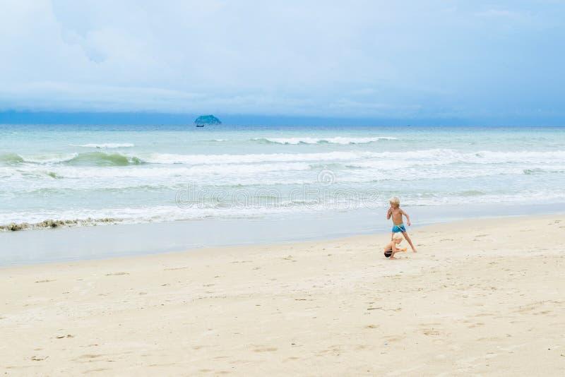 Dwa brata, chłopiec chodzi na białym piasku blisko morza przy plażą, Wietnam, Nha-trang zdjęcia stock