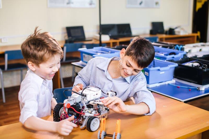 Dwa brata dzieciaka bawić się z robot zabawką przy szkolną robotyki klasą, salową obrazy stock