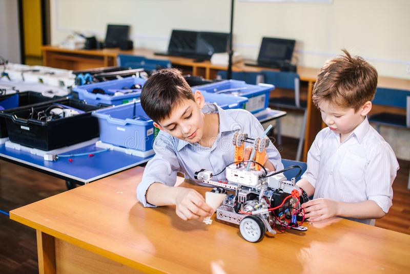 Dwa brata dzieciaka bawić się z robot zabawką przy szkolną robotyki klasą, salową obraz stock