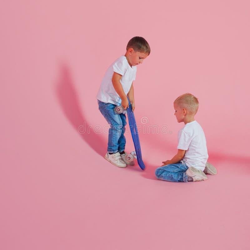 Dwa brata dzielą deskorolka Chłopiec z deskorolka Beginner łyżwiarka fotografia stock