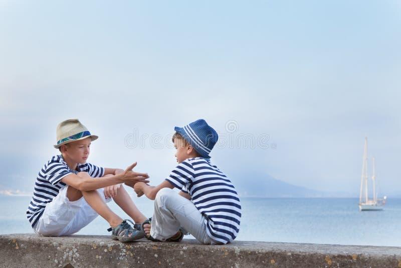 Dwa brata jednakowy obsiadanie na nabrzeżu, zdjęcia royalty free