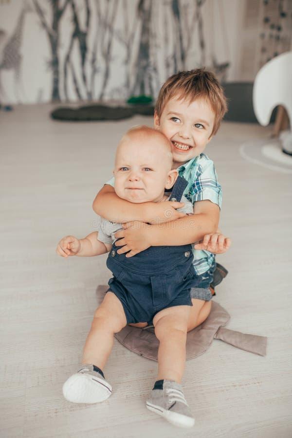 Dwa brata siedzą na dywanie i zabawę zdjęcia royalty free