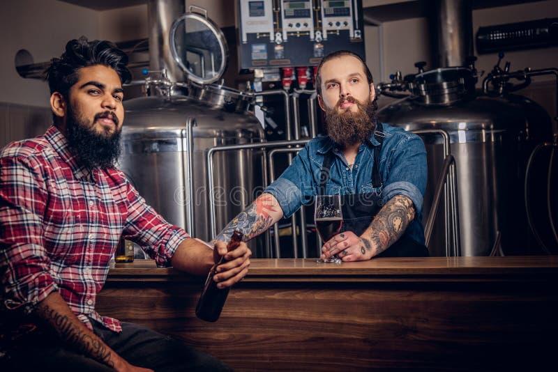 Dwa brodatego międzyrasowego przyjaciela piją rzemiosła piwo w browarze Tatuująca modnisia pracownika samiec w fartuchu pije piwo zdjęcia royalty free