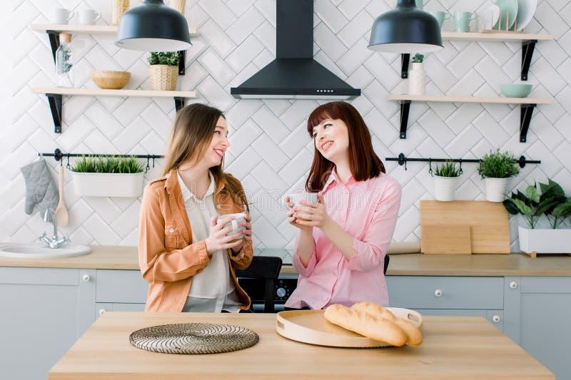 Dwa brunetek dziewczyn przyjaciel pije kawy lub zielonej herbaty opowiadać Para kobiety łasowania śniadanie wpólnie na kuchni obrazy stock
