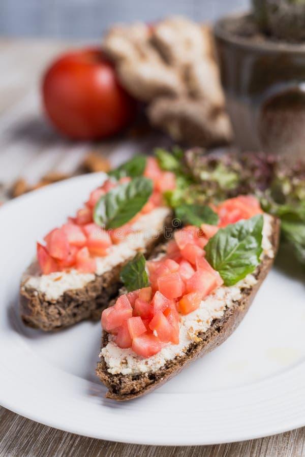 Dwa bruschettas, sałata, imbir i pomidoru, zdjęcia stock