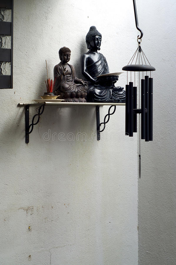 Dwa buddhas na półce z kadzidłowym i wiatrowym chime obrazy royalty free