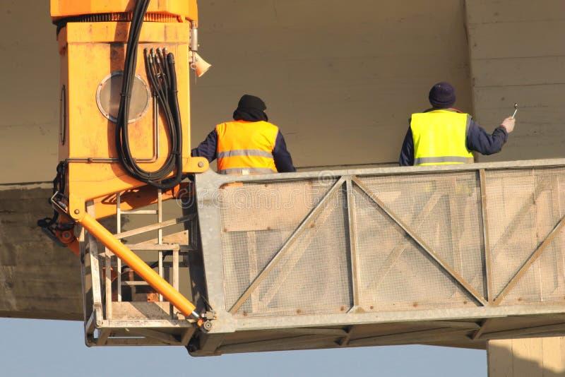 Dwa budowniczego w kolorze żółtym przy budową pracują na żurawiu fotografia stock