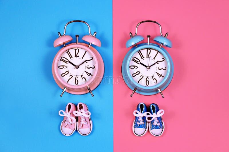 Dwa budzika na błękicie różowią tła, chłopiec lub dziewczyny pojęcie, zdjęcia stock