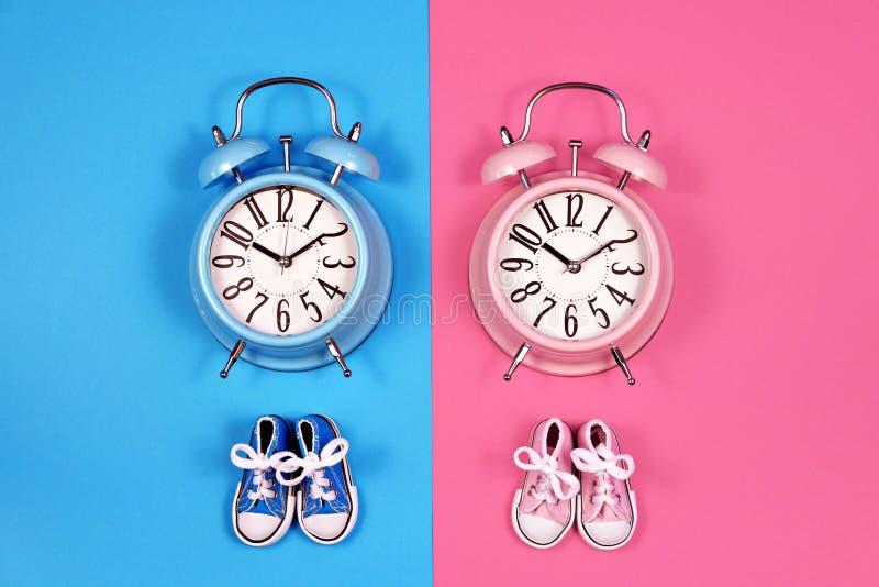 Dwa budzika na błękicie różowią tła, chłopiec lub dziewczyny pojęcie, obrazy stock