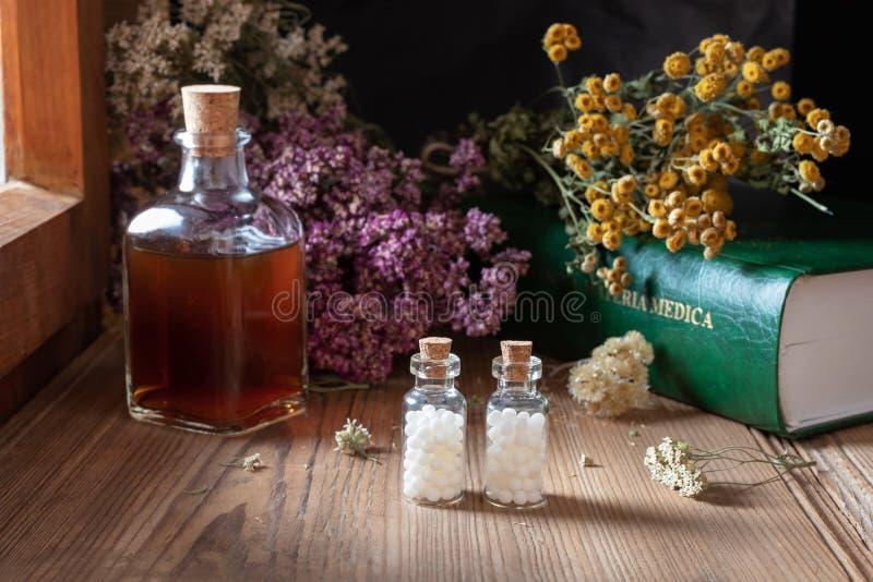 Dwa butelki homeopatyczne pigułki z wysuszonymi ziele i materia medica zdjęcie stock