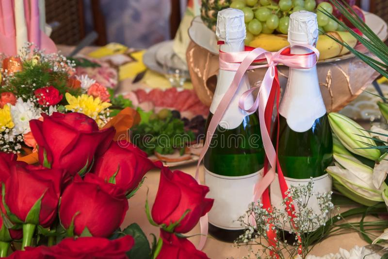 Dwa butelki szampan wiązali z faborkiem po środku bukietów kwiaty, wskazujący przyjęcia weselnego lub inny świątecznych zdjęcia stock