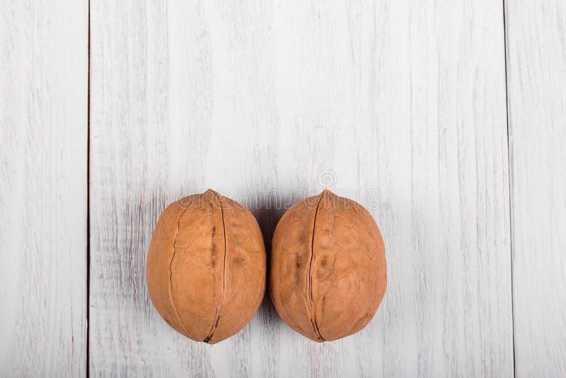 dwa całego orzecha włoskiego na drewnianym tle, zdrowy móżdżkowy jedzenie, orzech włoski na lekkim rocznika stole zdjęcia stock