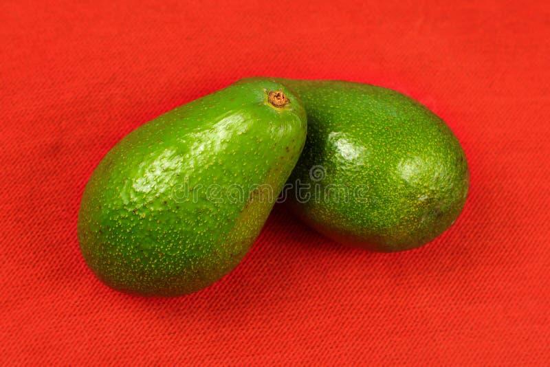 Dwa całej avocado bonkrety na czerwonym tablecloth obraz stock