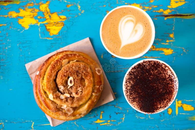 Dwa cappuccinos i cynamonowej ciasto rolka na obieraniu, pękającym błękit i kolor żółty malowali drewno z góry fotografia stock