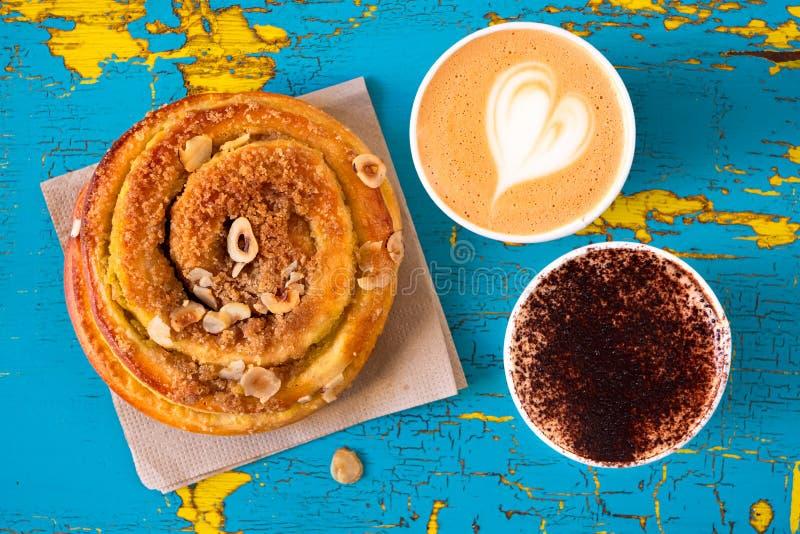 Dwa cappuccinos i cynamonowej ciasto rolka odizolowywający na obieraniu, pękającym błękit i kolor żółty malowali drewno z góry zdjęcie royalty free